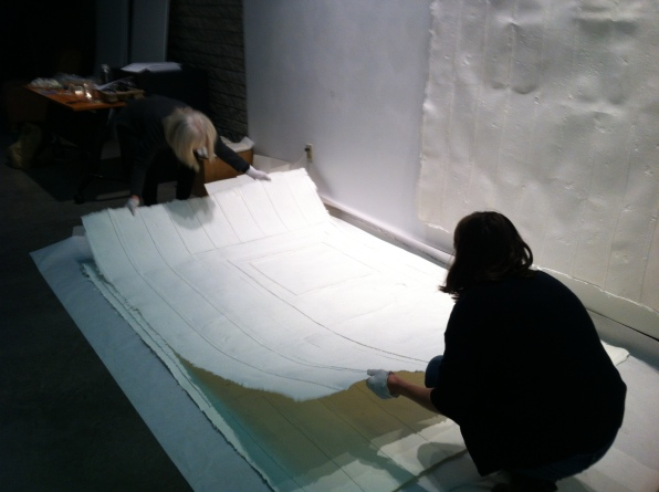 removing cast paper walls from crate for installation at the Two Rivers Gallery.
